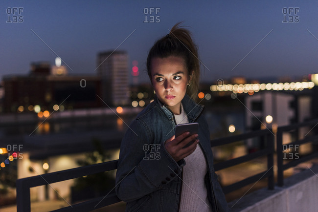Young woman in the city with cell phone in the evening
