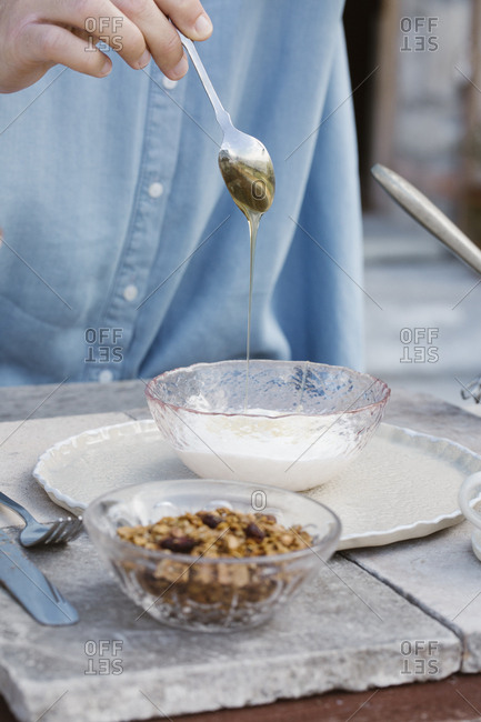 Italy- woman dripping honey on natural yoghurt at breakfast table on terrace- partial view
