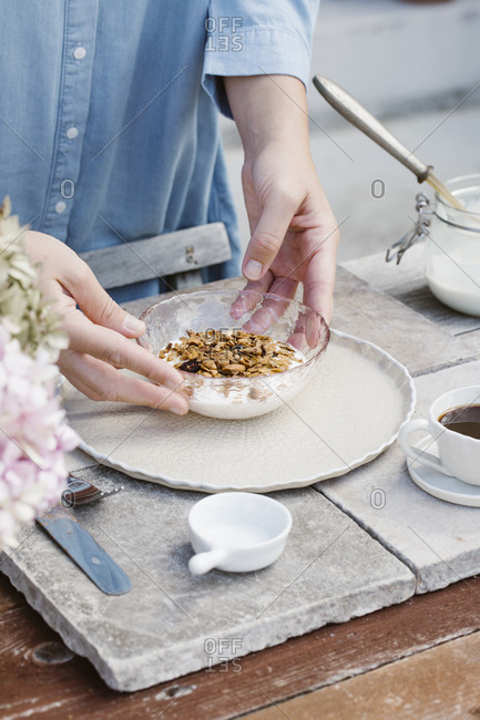 Italy- woman arranging bowl of granola on breakfast table- partial view