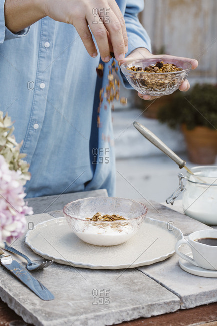 Italy- woman preparing breakfast on terrace- partial view