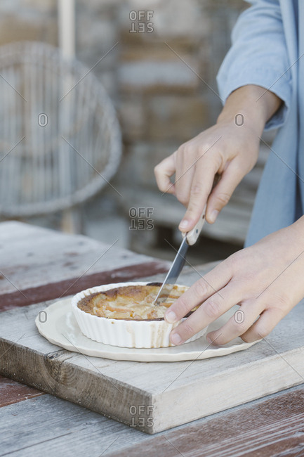 Italy- woman's hands cutting tartlet