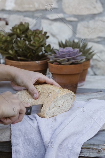 Italy- woman's hand cutting bread on terrace