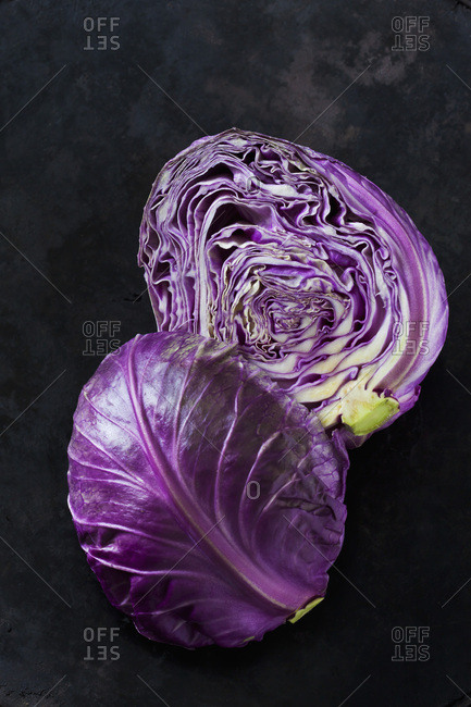 Two halves of purple Sweetheart Cabbage on dark ground