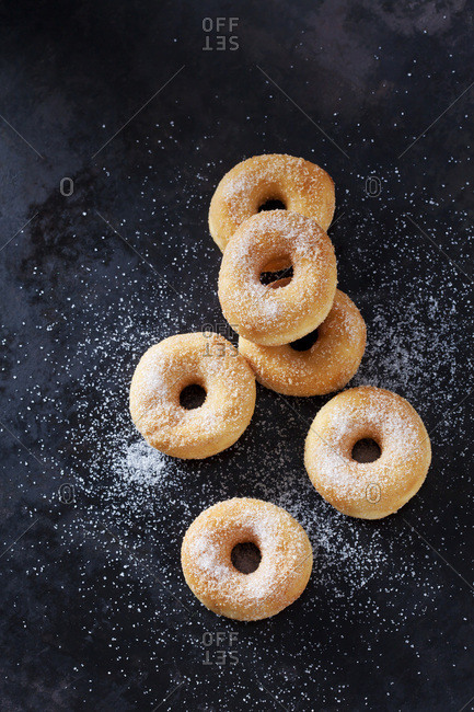 Six mini doughnuts sprinkled with sugar on dark ground