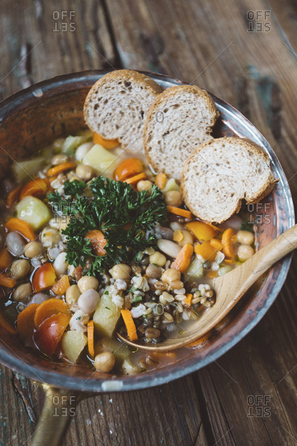 Mediterranean soup and bread slices in copper pot