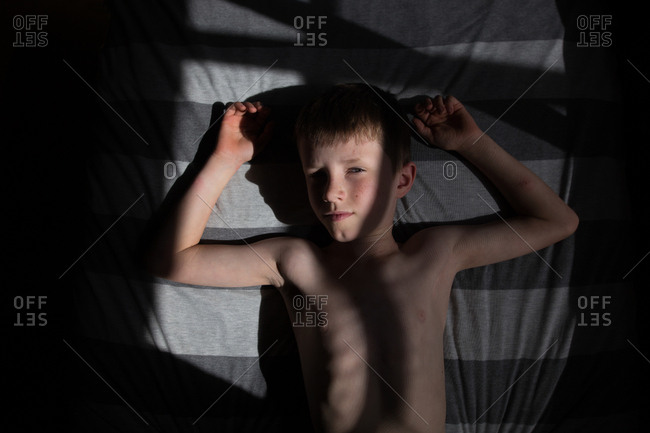 Boy resting on bed in the dark