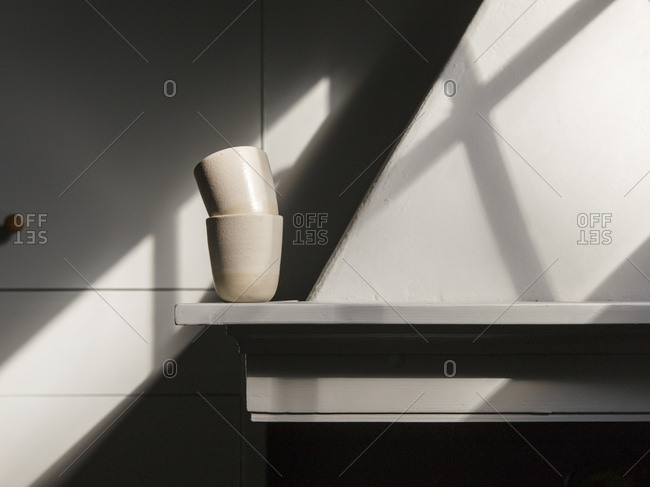 Two ceramic cups on a shelf