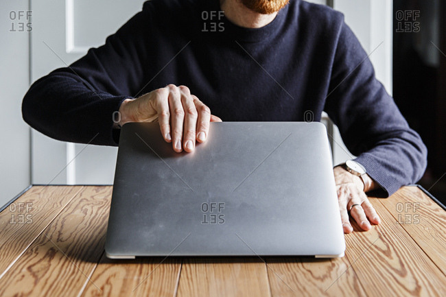 A man working on a laptop computer in the clean interior of a design country house