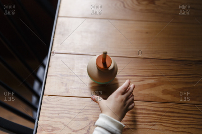 Toddler reaches for a spinning toy top on a table