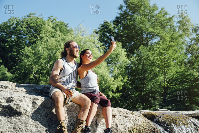 Caucasian couple posing for cell phone selfie on rocks