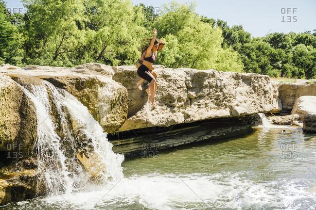 Caucasian couple jumping off rocks near waterfalls