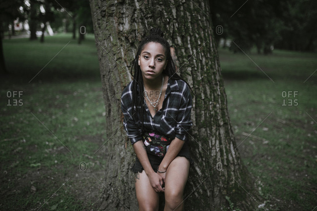Portrait of serious African American woman leaning on tree