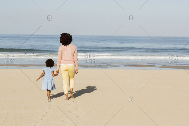 Black mother and daughter walking on beach