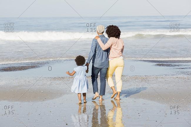 Black family walking on beach