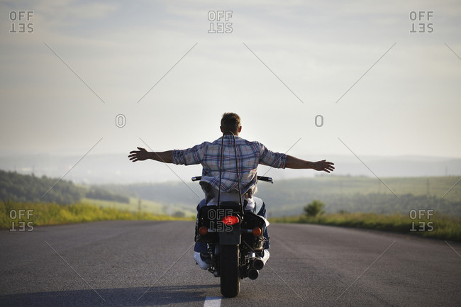 Caucasian man riding motorcycle with arms outstretched
