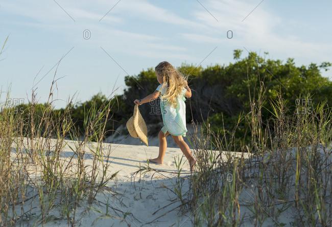 Caucasian girl walking on beach holding hat