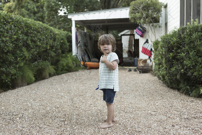 Portrait of curious Caucasian boy standing in driveway