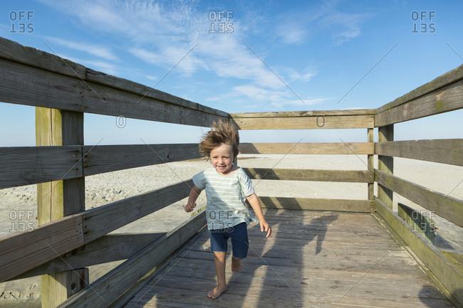 Caucasian boy walking on windy boardwalk