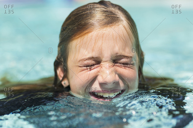 Caucasian girl swimming with eyes closed