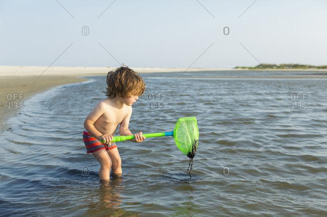 Caucasian boy wading in ocean holding