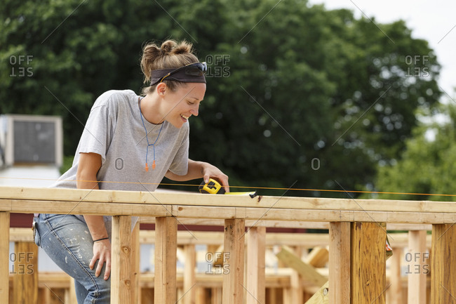Caucasian woman measuring at construction site