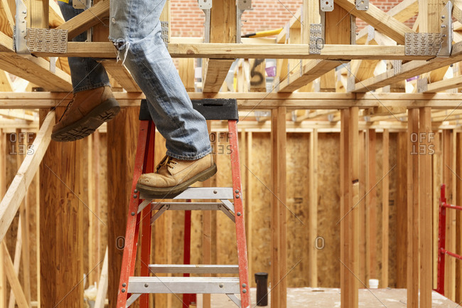 Legs of black man on ladder at construction site
