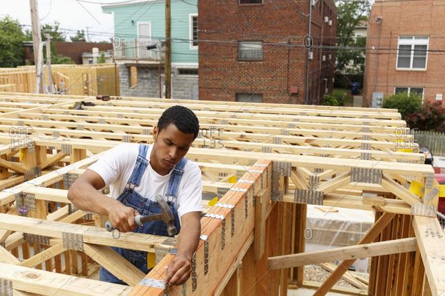 Mixed race man hammering nail at construction site