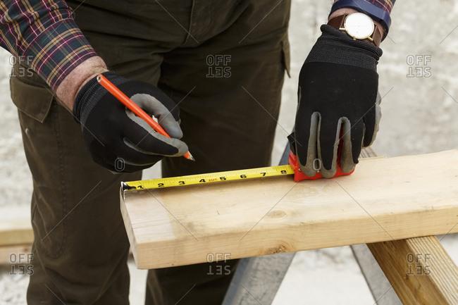 Caucasian man measuring lumber