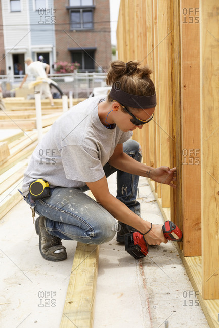 Caucasian woman drilling lumber at construction site