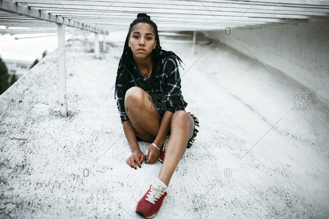 Portrait of serious African American woman sitting on concrete