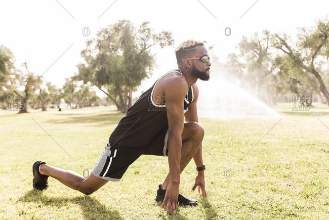 Black man crouching in park stretching legs