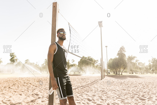 Black man leaning on beach volleyball net