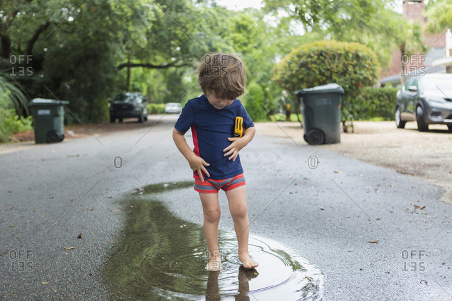 Caucasian boy standing in puddle on street