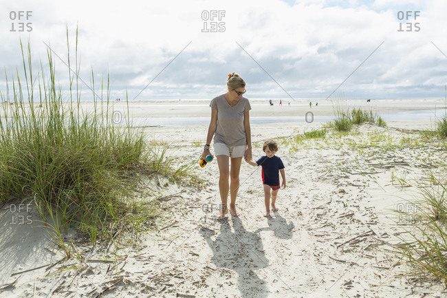 Caucasian mother and son walking on beach