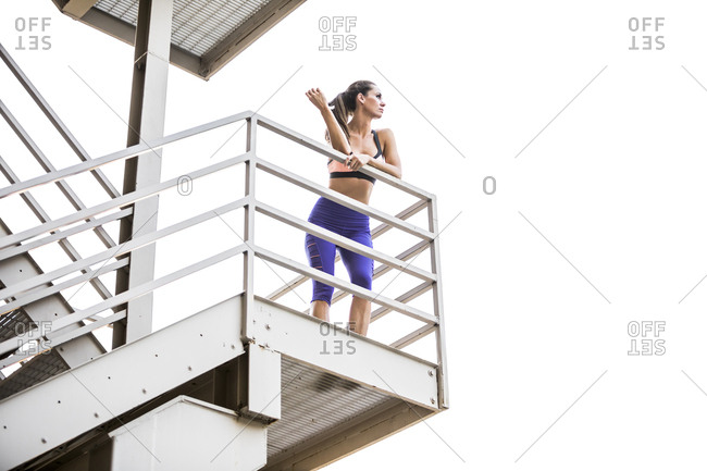 Caucasian woman leaning on urban staircase