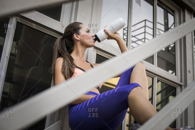 Caucasian woman drinking water on urban staircase