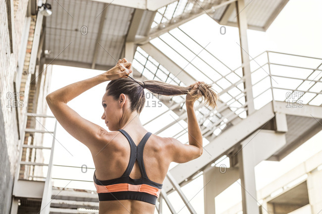 Caucasian woman tying hair in ponytail