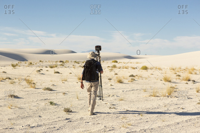 Rear view of Caucasian photographer carrying tripod in desert