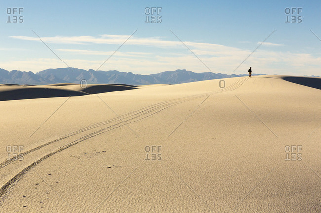 Trail leading to distant Caucasian man in desert