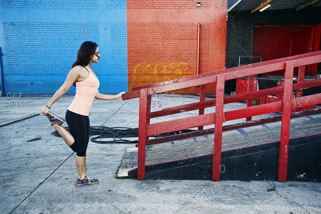 Mixed race woman stretching leg at loading dock