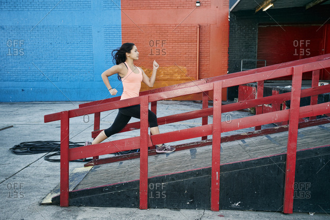 Mixed race woman running up loading dock