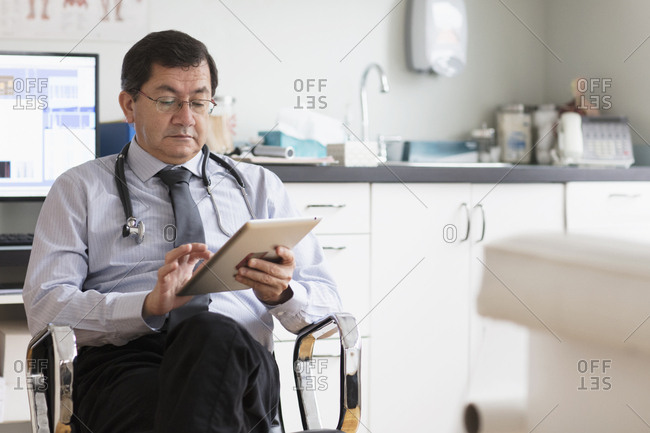 Hispanic doctor reading digital tablet