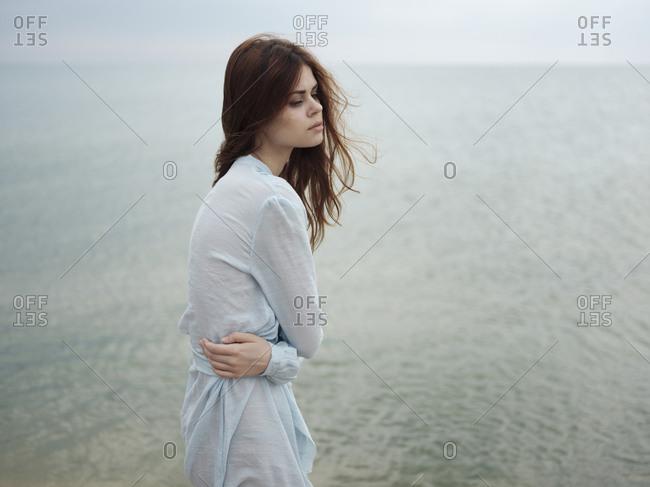 Troubled Caucasian woman standing near ocean