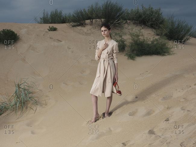 Caucasian woman wearing dress on beach carrying shoes