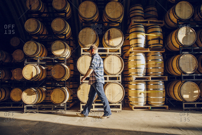 Caucasian man walking near barrels in distillery