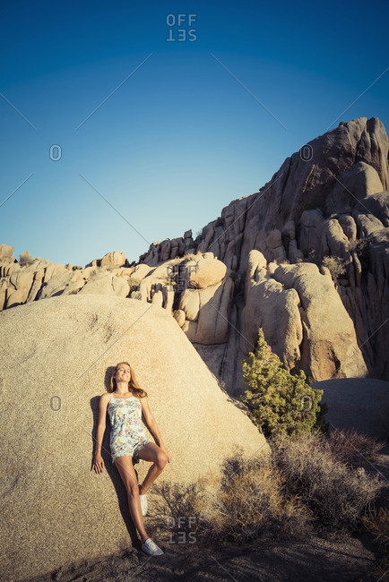 Hispanic woman leaning on rock