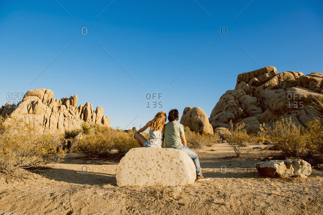 Hispanic couple sitting on the rock in desert