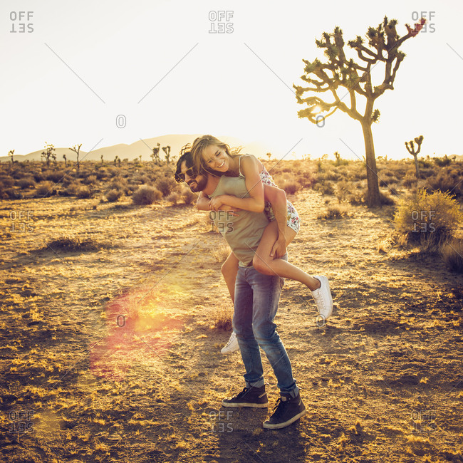 Hispanic man carrying a woman piggyback in desert