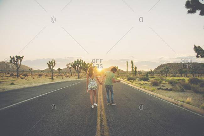 Hispanic couple holding hands walking in street