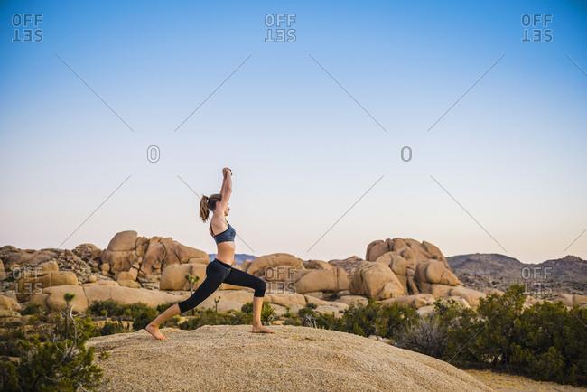 Hispanic woman performing yoga in desert